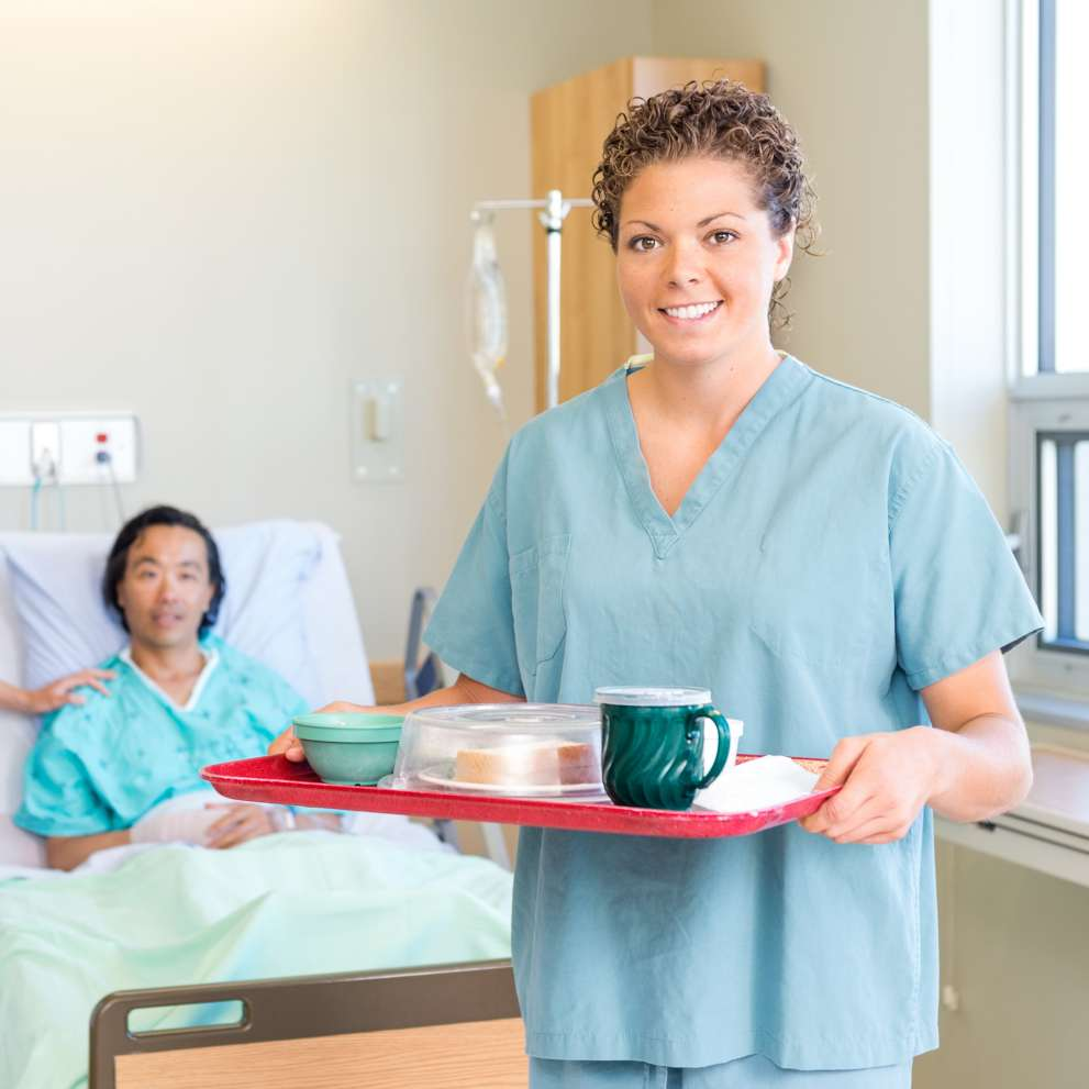 A Patient Care Technician brings a tray of food to a patient in a hospital bed