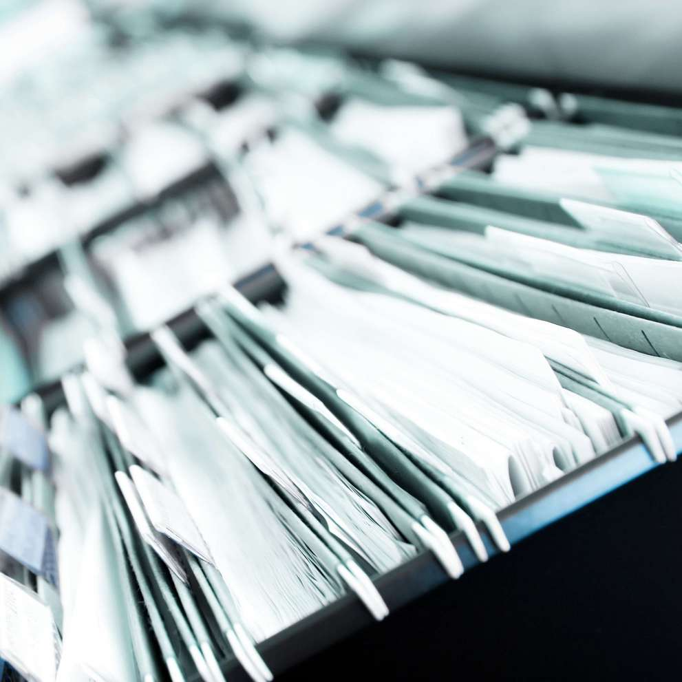 close up of open filing cabinet full of files