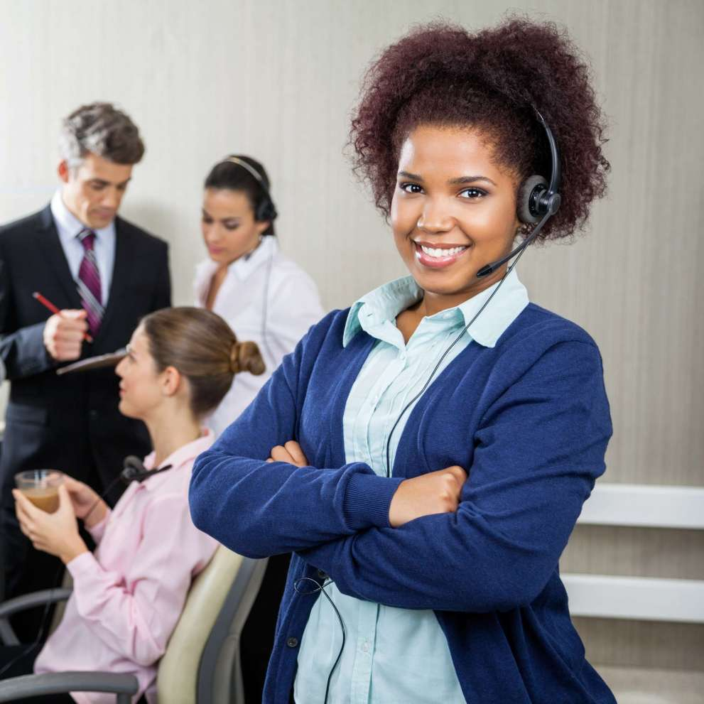woman at a call center wearing a headset and smiling with her arms crossed