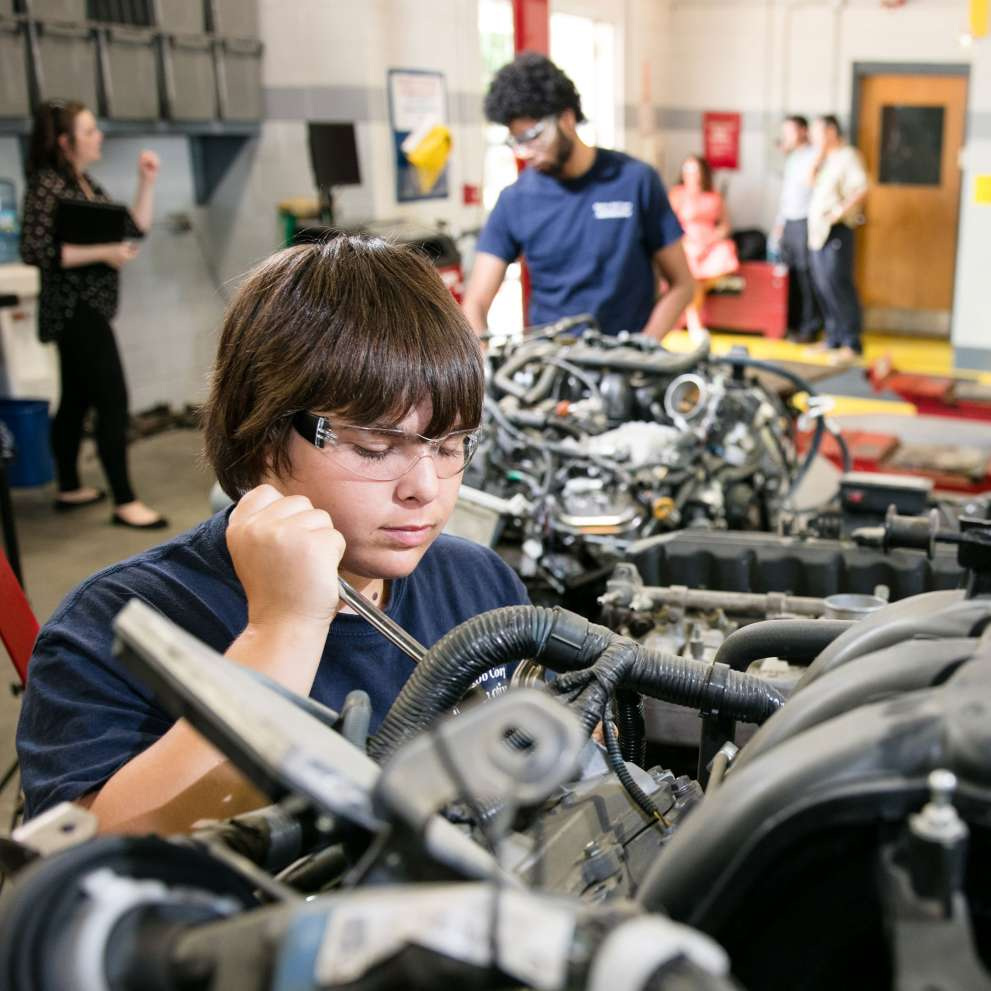 An Automotive and General Service Technician works on an engine