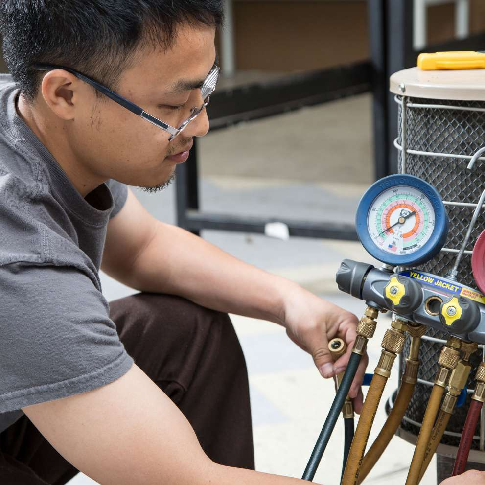 HVAC student working on a air conditioner