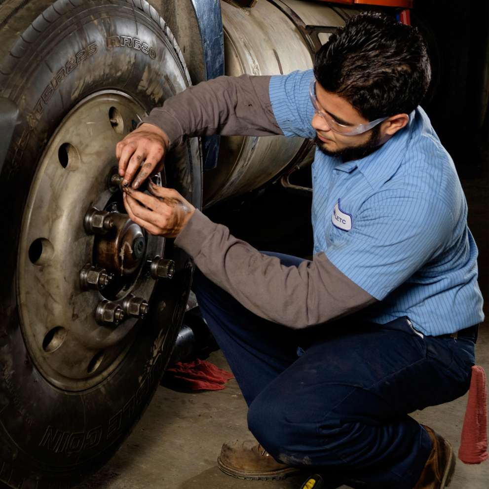 Job Corps student working on large tire