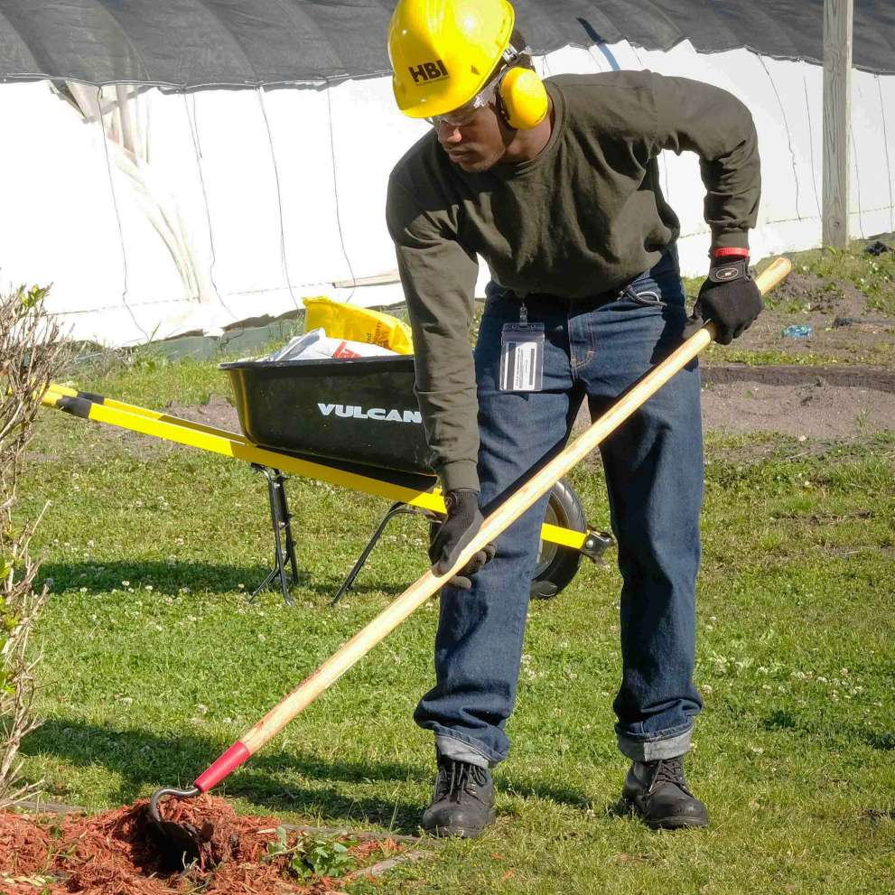 Landscaper moves much around the base of a shrub with a hoe