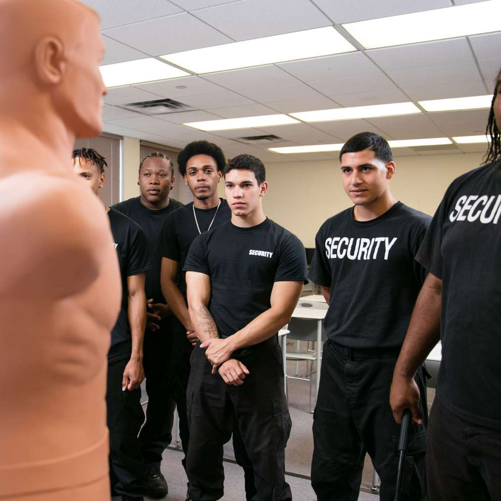 Security students in class with instructor and security dummy