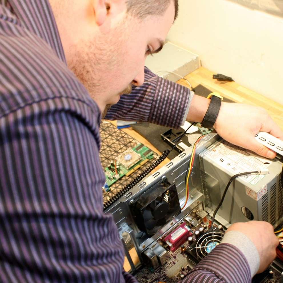 A computer technician repairs a desktop computer.