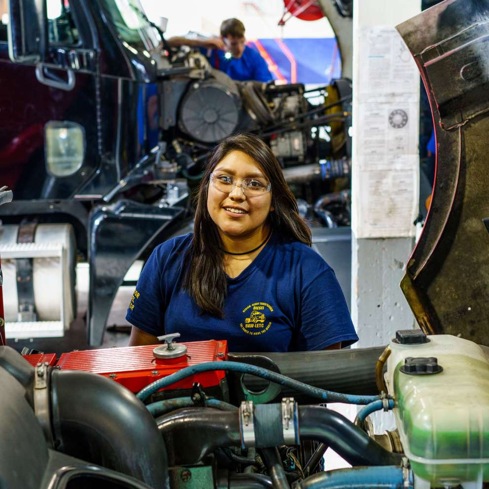 A Job Corps student inspects a diesel engine.
