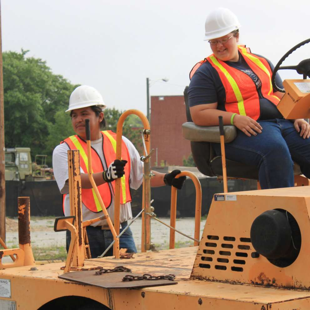 Advanced Asphalt Paving workers lay fresh asphalt along a stretch of road.