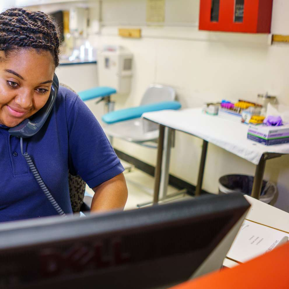 A medical administrative assistant answers a telephone call.