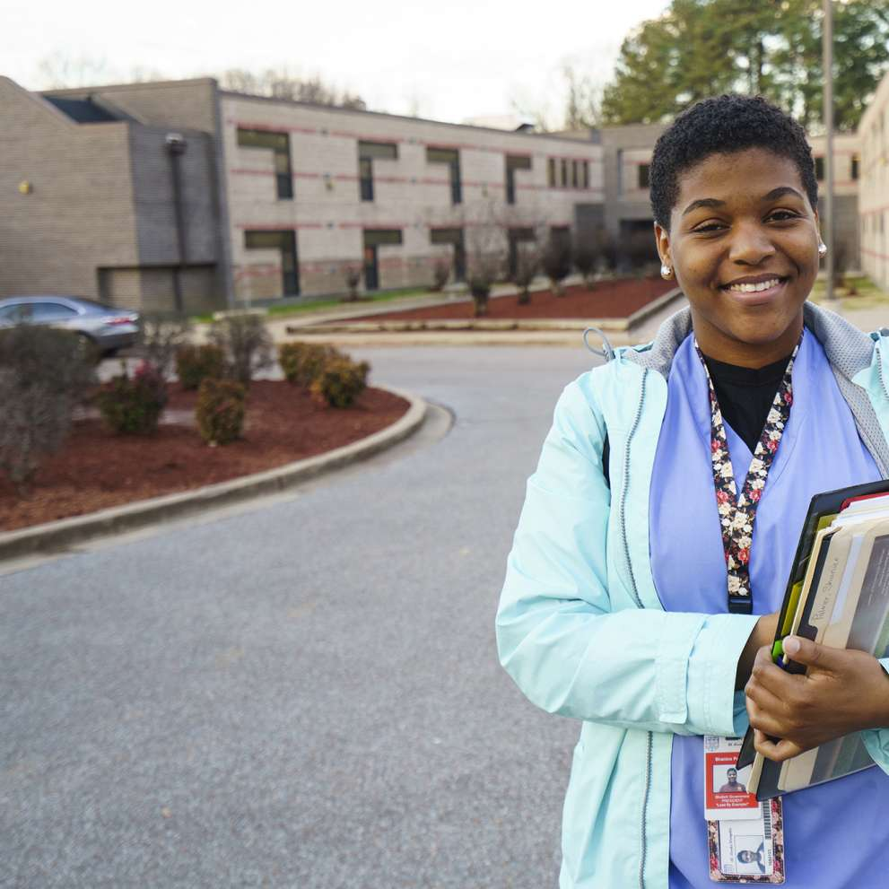 Estudiante de Job Corps sosteniendo una carpeta en el estacionamiento del campus
