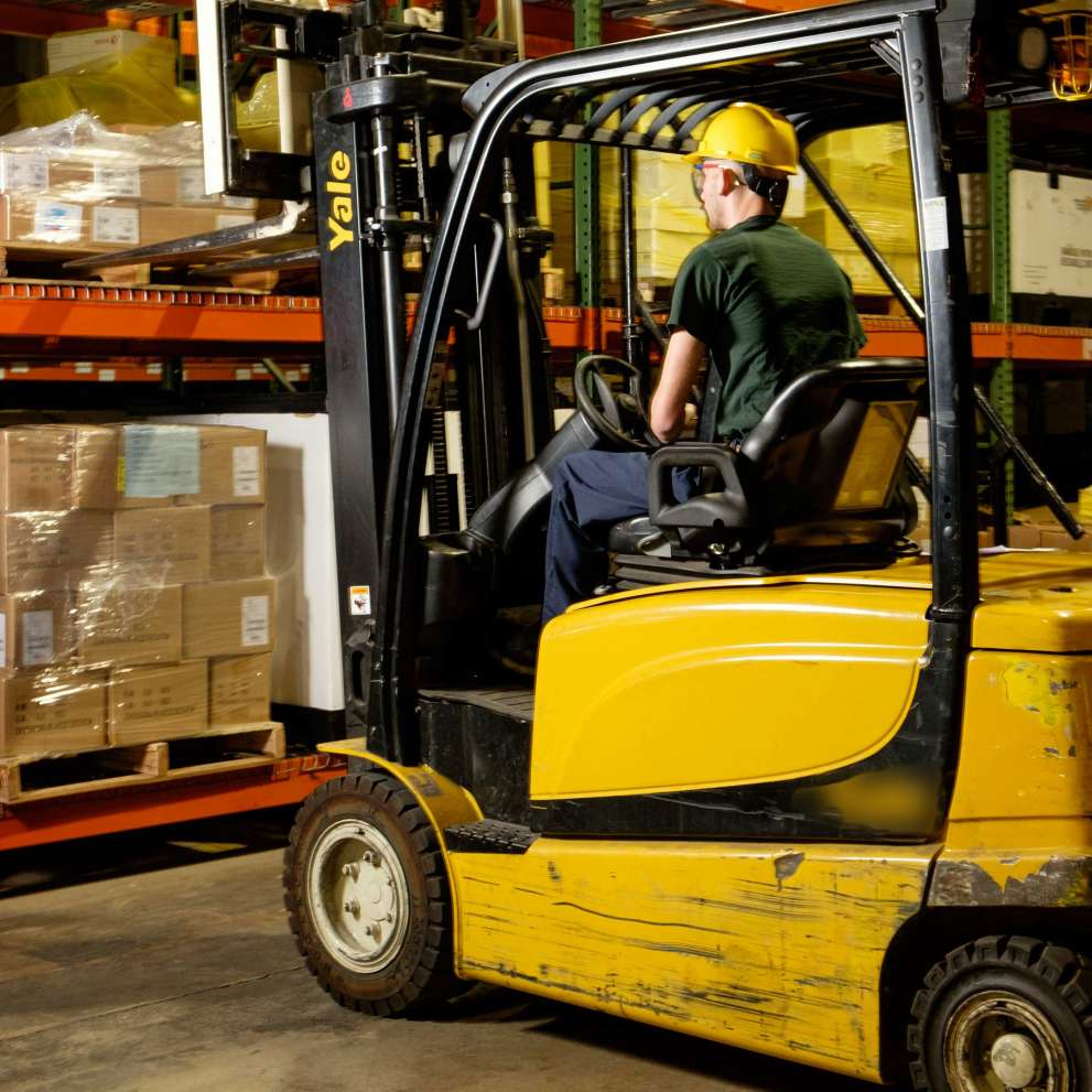A Material and Distribution Operations worker moves goods with a forklift