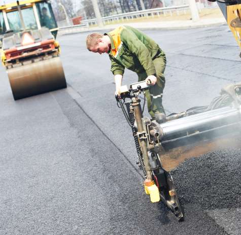 An asphalt paver lays hot asphalt along a stretch of road.