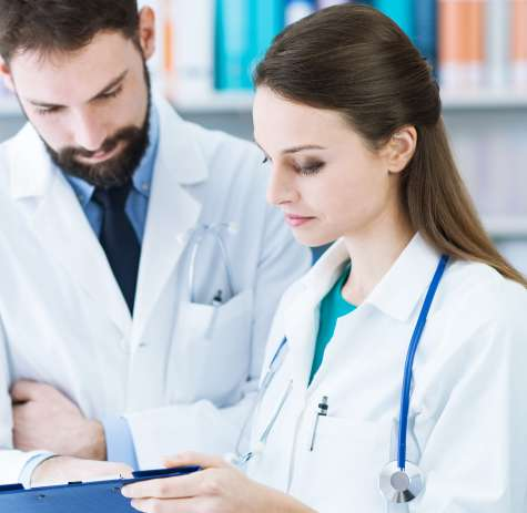 A Licensed Practical/Vocational Nurse consults with a doctor on the care a patient needs.