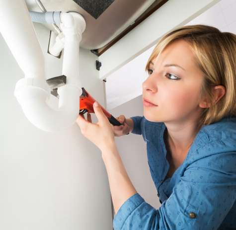 A plumber installs a j-pipe.
