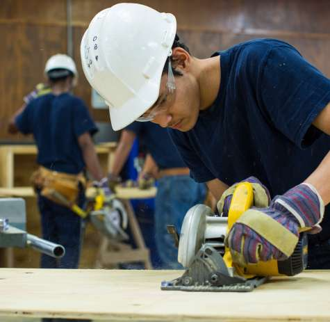 A carpenter uses a saw to cut a board to his specifications.