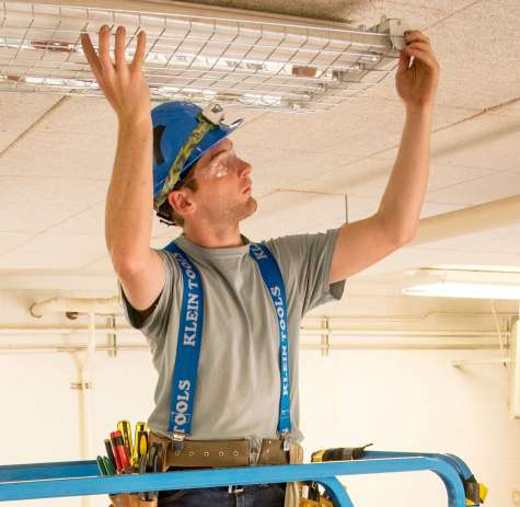 Construction craft laborer installing ceiling lights