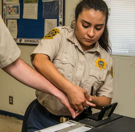 Corrections Officer student practicing taking finger prints
