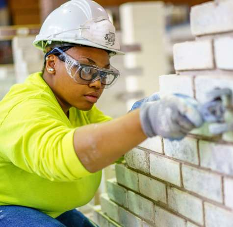 A bricklayer works with bricks and mortar.