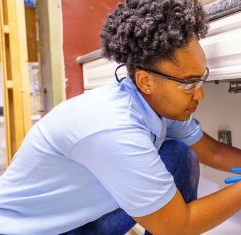 A Job Corps student performs a plumbing repair