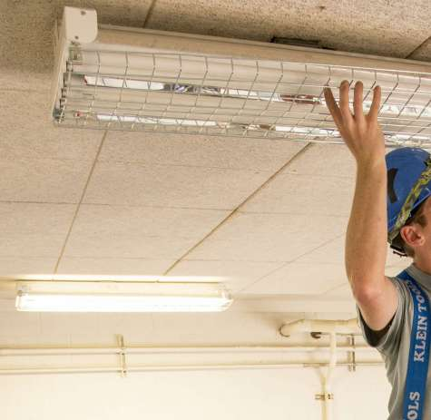 A man adjusts a ceiling light fixture