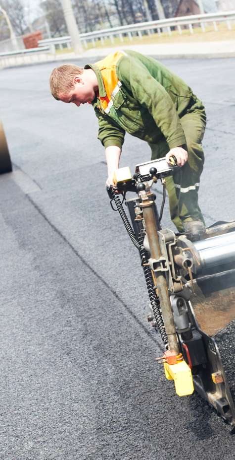 An asphalt paver lays hot asphalt along a stretch of road.