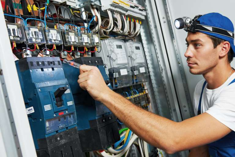 An electrician at work at a circuit board.