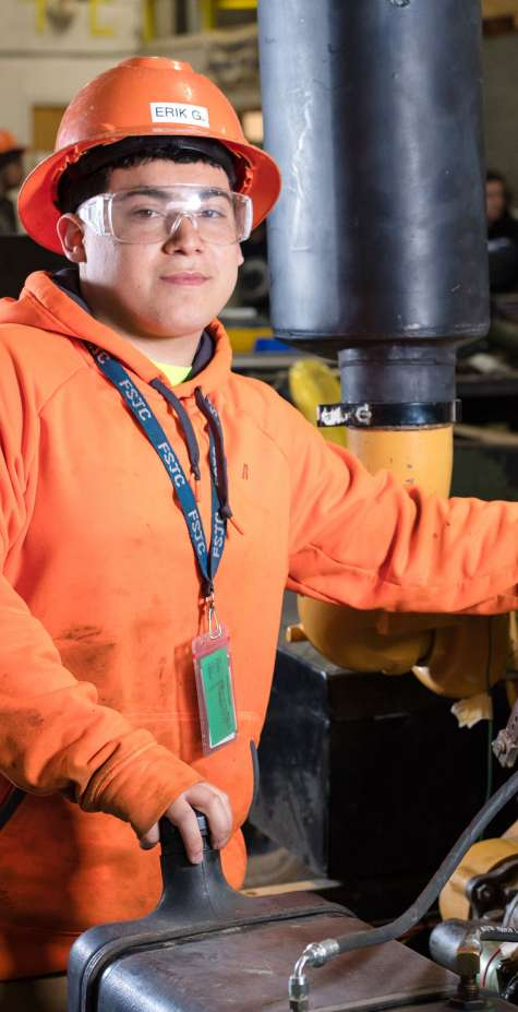 A machine repair mechanic works on a piece of heavy equipment.