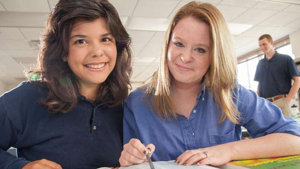 Two Job Corps students sitting at a table, studying and smiling