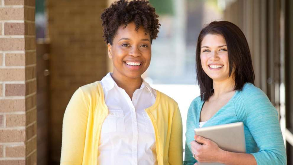 Two smiling students pose for a photo between classes