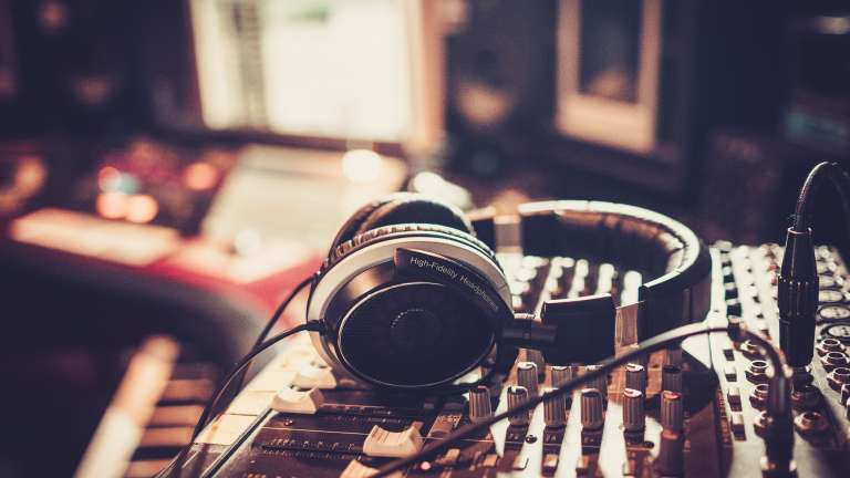 A pair of headphones rests on a soundboard