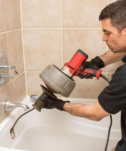 A plumber uses a drain cleaning tool on a shower drain.