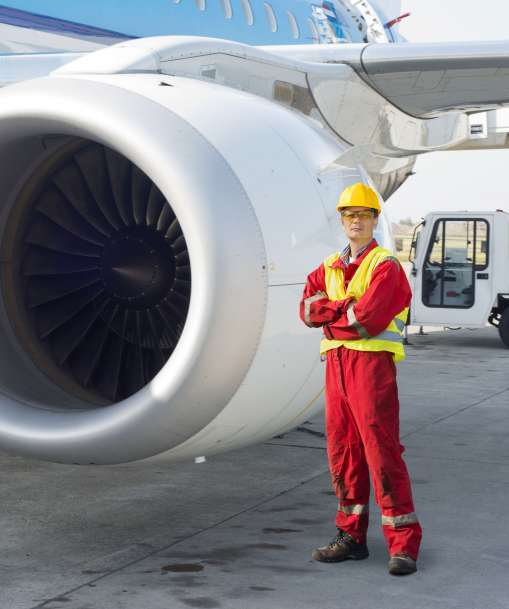 A transportation worker poses next to a jet engine.
