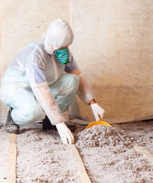 A weatherization technician adds insulation to an attic