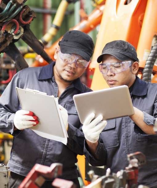 A pair of manufacturing technicians compare notes on a clipboard and a tablet.