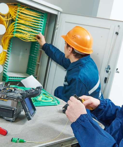 A pair of Network Cable Installation technicians arrange cables in a structured media enclosure