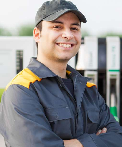 A Petroleum Service Technician poses next to fuel pumps.