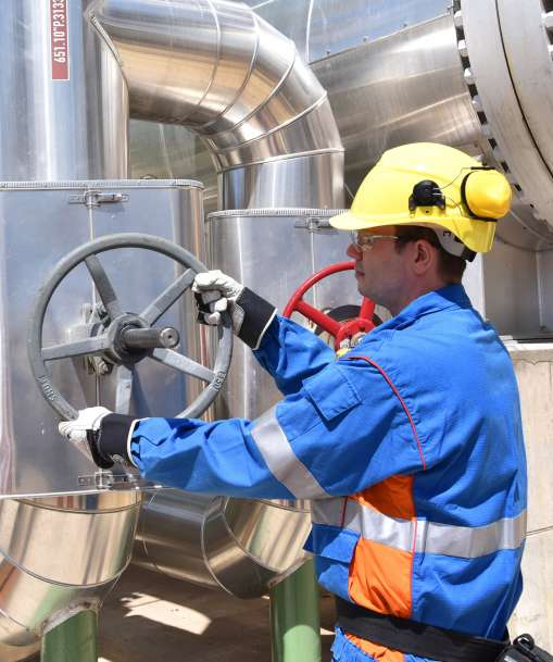 A Stationary Engineer turns a valve wheel at a plant.