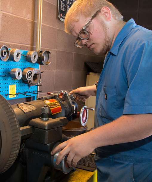 job corps student working with auto parts automotive and machine repair