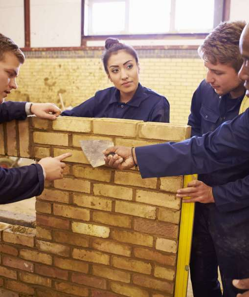 A Bricklaying instructor teaches a group of students the tricks of the trade