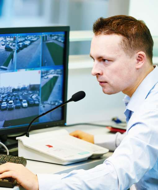 Security guard looking at surveillance screens