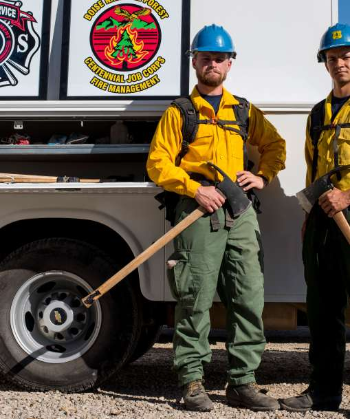 Wildland firefighters stand with firefighting gear