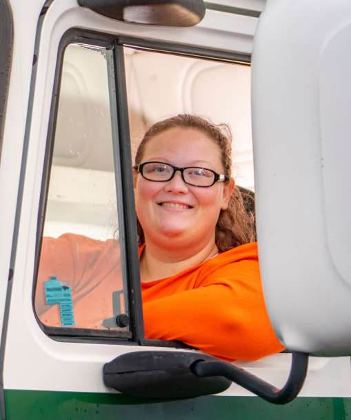 A driver sits in the cab of a large truck.