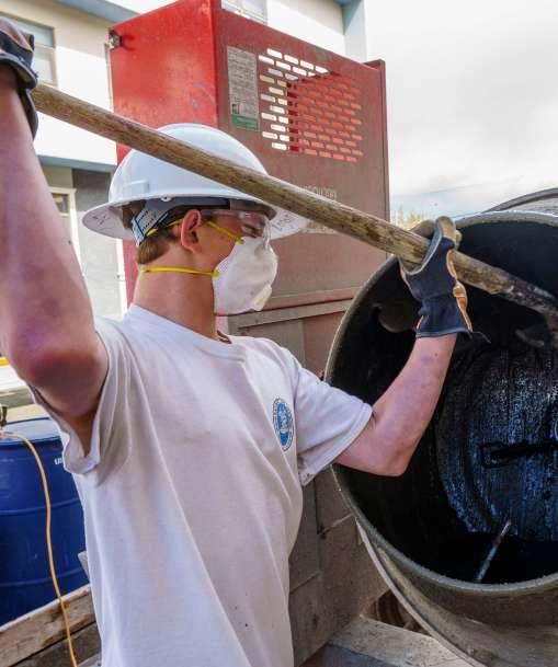 A cement masonry worker mixes a batch of cement.