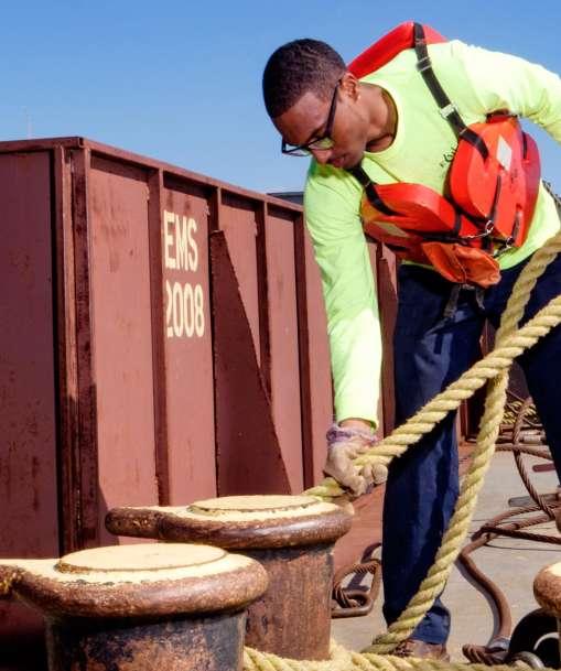 A deckhand handles rigging