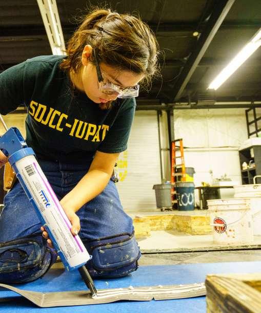 A floor covering student installs flooring