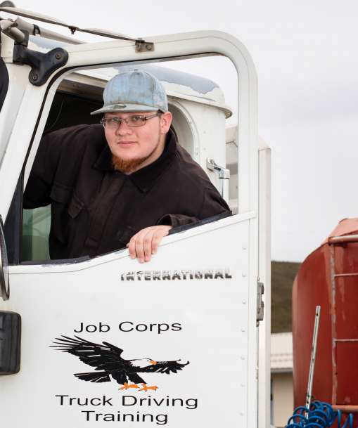 Job Corps student smiles from the cab of a heavy truck