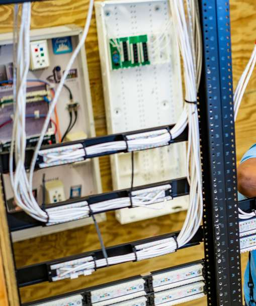 A network cable installation technician arranges telecommunications cables