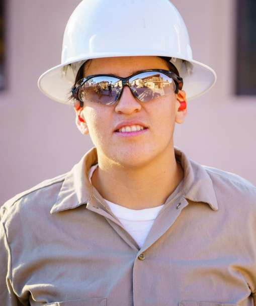 A Job Corps student wearing a hard hat and eye protection