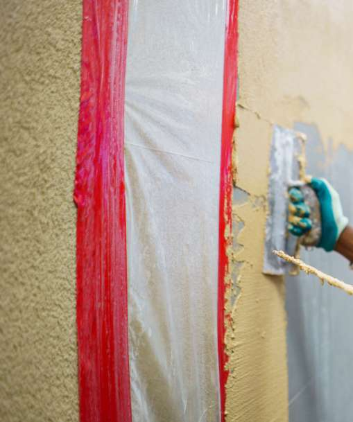 A plastering technician applies a coat to a wall.