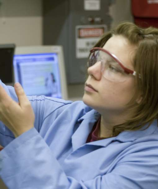 A wastewater management student holds a water sample