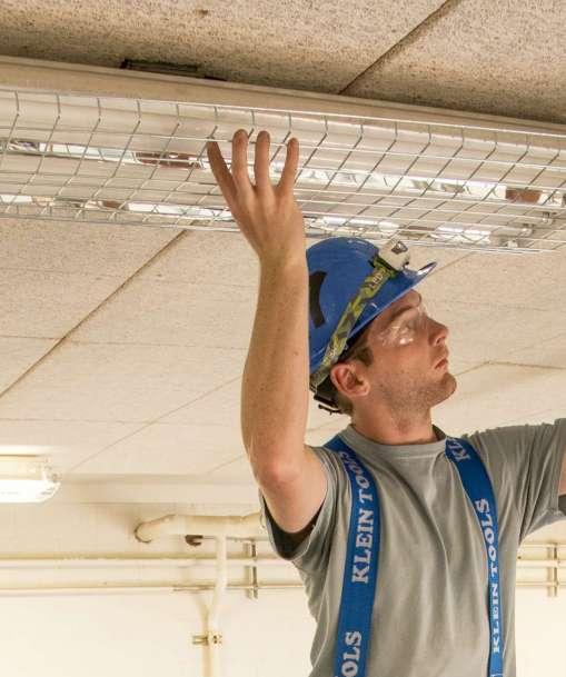 A man adjusts a ceiling light fixture.